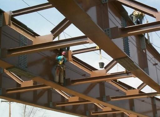Men standing on bridge beams