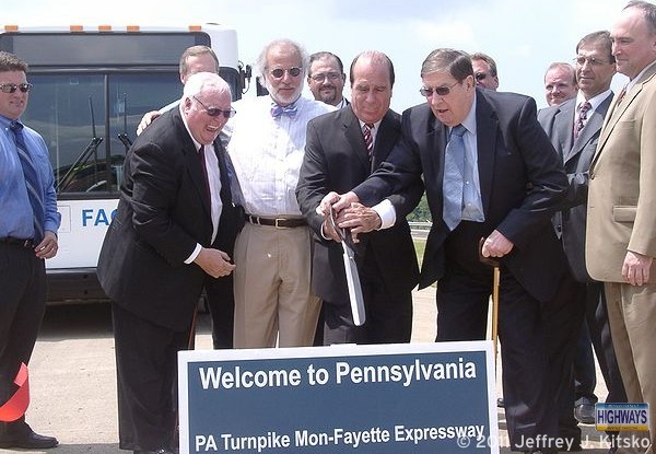 Local and state officials cutting the ribbon for PA Turnpike 43 at the state line